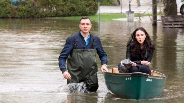 Residents make their way through a flooded streets in Laval, Que./Photo via Ryan Remiorz,Canadian Press