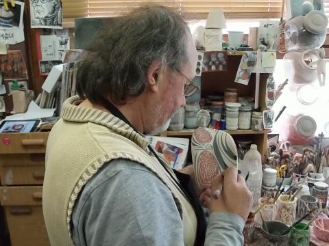 Otero Regal pintando una pieza de cerámica. Fotografía: Císimo Rabanedo