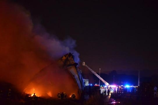 Bombeiros combatem as chamas.