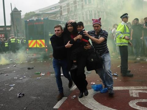A young family run for cover as West Ham fans riot in the streets (picture by Ed Lodger)