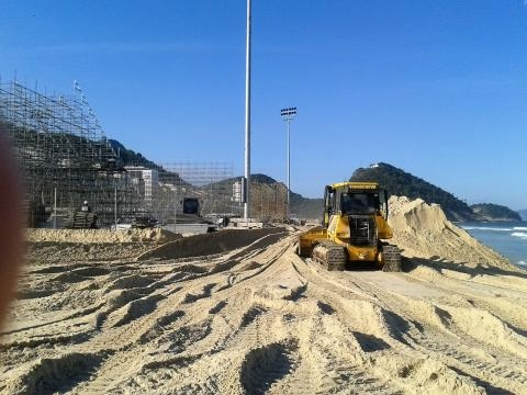 Tratores erguem paredes de areia para conter o avanço do mar