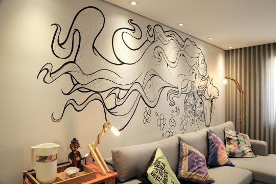 Decoração com wall painting na sala de estar e TV (Divulgação).
