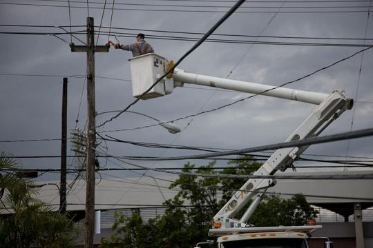 Electric company repairing a power pole in Puerto Rico (Image credit – Andrea Booher – Wikimedia Commons)