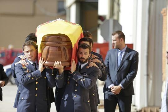 Apesadumbrados los companeros del capitán portan el feretro de su compañero
