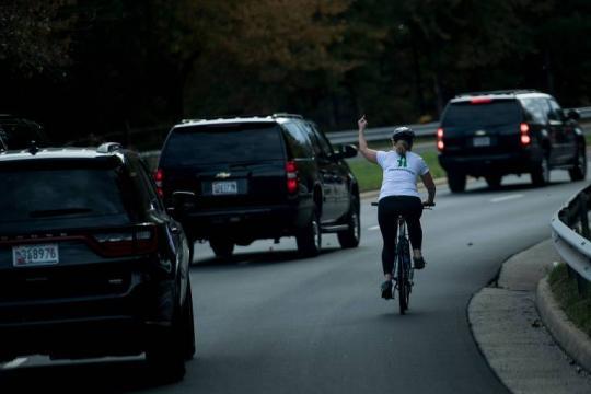 Juli Briskman no momento do gesto obsceno aos carros da comitiva de Donald Trump