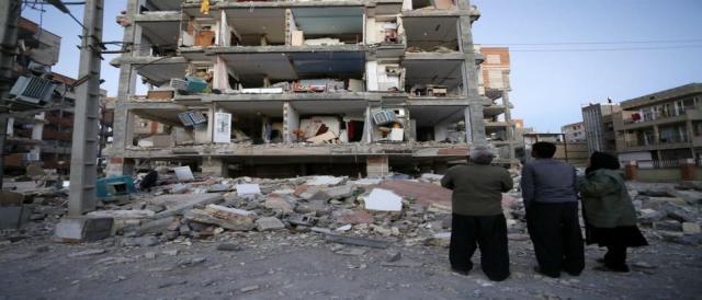 Moradores observam prédio destruído por terremoto na região de Sarpol-e Zahab, no Irã.
