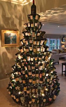 Aposte em garrafas de vidro para montar sua árvore de natal, encaixando na estrutura similar ao formato da árvore.