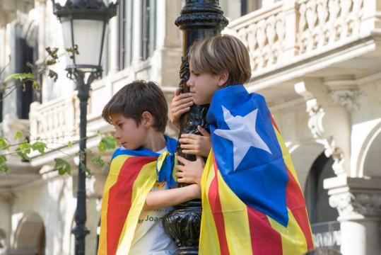 Boys dressed in Catalan independence flags, hang onto a pole during recent protests.