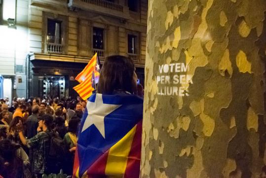 Women dressed in the Catalan independence flag stands next to a spray painted tree that reads in Catalan