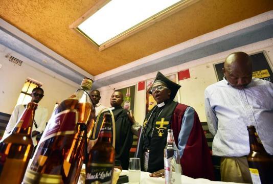 O bispo se coloca atrás de uma garrafa de uísque de 4,5 litros para presidir as celebrações religiosas