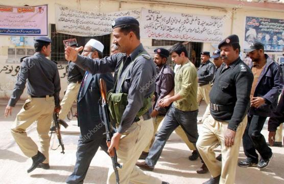 Police officials escorting Shahrukh Jatoi as he is taken by the ... - depositphotos.com