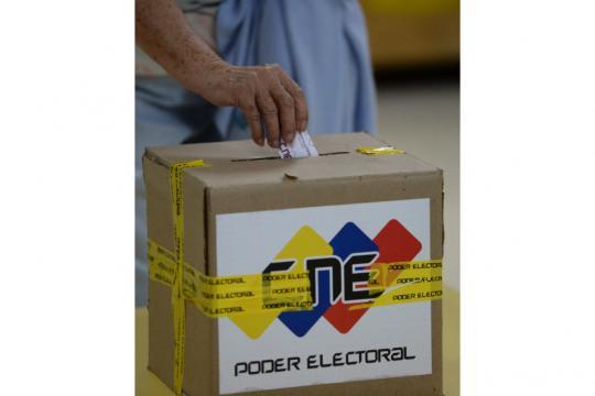 Votante depositando su papeleta en la caja del CNE