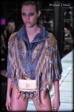 A model in a silver-and-gold mesh jacket walks the runway for Laurel DeWitt at Scottsdale Fashion Week. (Photo copyright 2017 Michael J Wells)