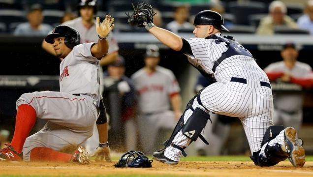 Xander Bogaerts (izq.) anota durante un partido en Yankee Stadium, la temporada pasada. (vía twitter - jm_yaqui).