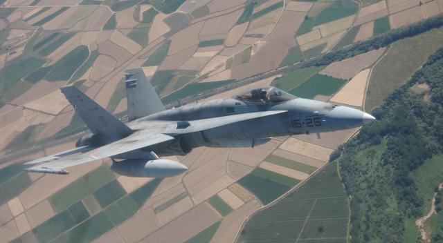 El F-18 se recorta sobre los cuadros sembrados en tierra.