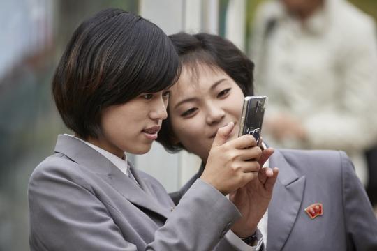Due ragazze con uno smartphone a Pyongyang
