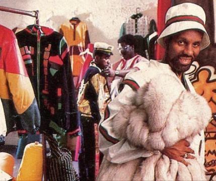 1989, Dapper Dan posa nella sua boutique con un abbigliamento Gucci e una pelliccia