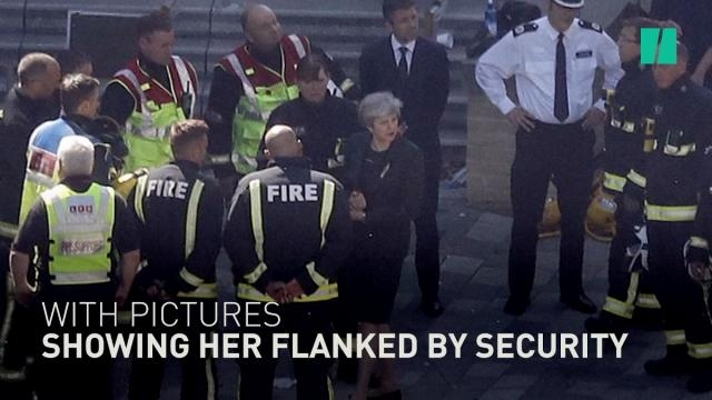 British Prime Minister Theresa May surrounded by security at Grenfell Tower. / Image by HuffPostUK via YouTube:https://youtu.be/qArHC9c1arE