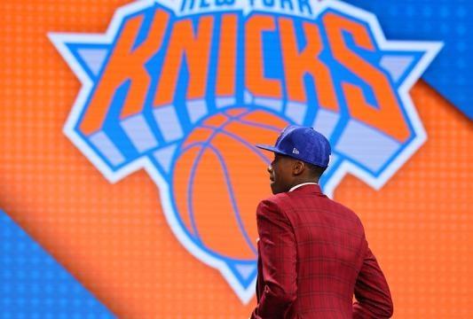 Frank Ntilikina lors de la draft, devant le logo de sa future équipe NBA, les New York Knicks.