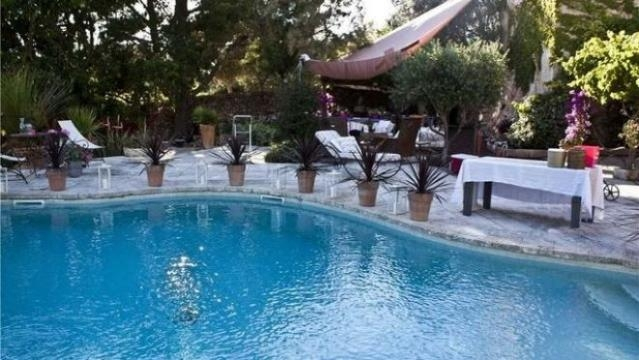 Vista de la piscina rodeada de jardín y con todas las comodidades para relajarse.