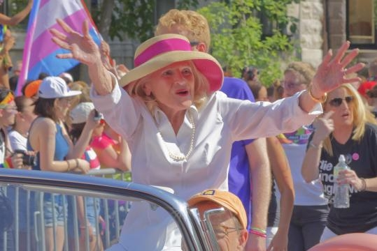 Windsor waves to a crowd of people during a parade.