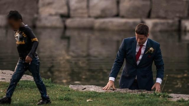 A Canadian couple was enjoying their wedding shoot when the groom rescued a young boy from a nearby pond [Photo: YouTube/1010 Wins]