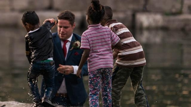 A couple was enjoying their wedding shoot when the groom rescued a young boy from a nearby pond [Photo: YouTube/1010 Wins]