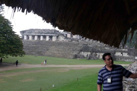 Uno de varios jóvenes haciendo la labor del guía ante las ruinas Mayas.