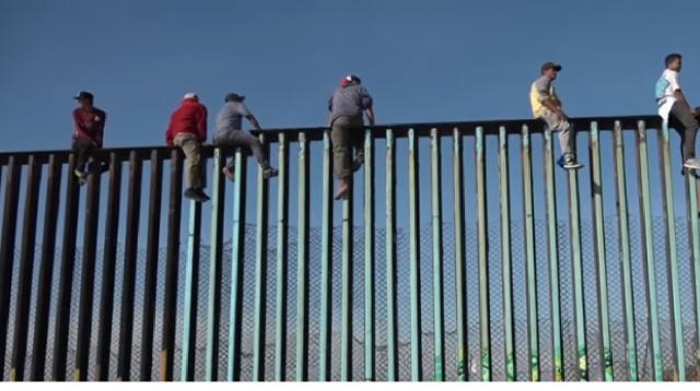 Dozens of migrants climb border fence near Tijuana, Mexico. [Image source/RT YouTube video]