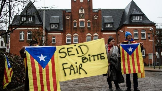 Varias personas sostienen esteladas y una pancarta en la que se puede leer