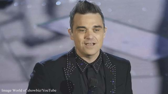 After giving the middle finger at the opening of the World Cup in Russia, Robbie Williams admits to a problem. [Image World of Showbiz/YouTube\