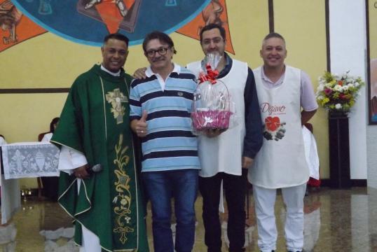 Padre Marcos, que ministrou workshop político, e agentes da Pastoral do Dízimo, presenteando dizimista.
