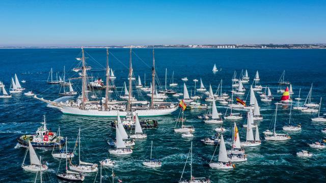 El Juan Sebastian Elcano sale de puerto escoltado por docenas de pequeños veleros