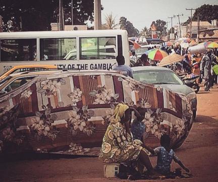 Mujer y niñas esperando el transporte público en Serrekunda