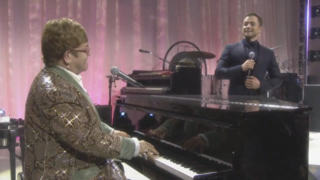 Elton John smiles as Taron Egerton sings a duet with him. [Image AMC Theatres/YouTube]