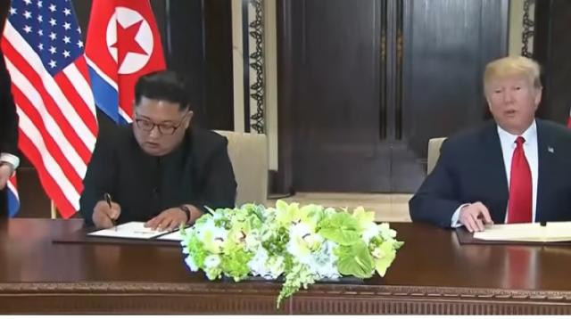 Kim and Trump sign joint agreement at close of Singapore summit. [Image source/Guardian News YouTube video]