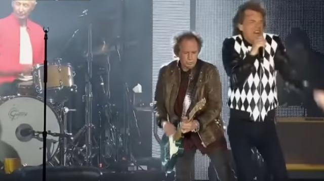 Mick Jagger struts on stage in first concert after heart surgery. [Image source/Guardian News YouTube video]