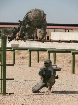 Mientras un compañero pasa el obstáculo otro lo cubre con su arma