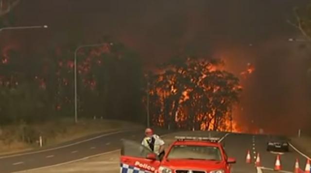Raging Australian bushfire force residents to water's edge. [Image source/Global News YouTube video]