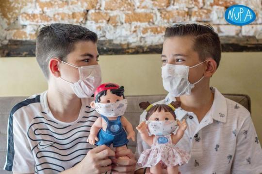 Dos niños de la Asociación NUPA posan con las muñecas solidarias.