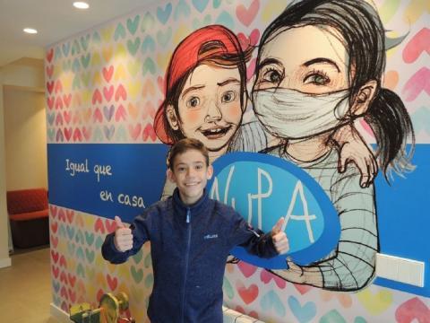 Un niño de la Asociación posa delante de un mural de NUPA.