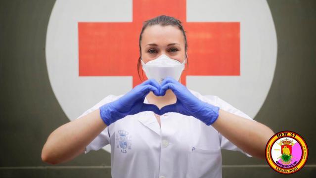 Agradecimiento: Una sanitaria hace el gesto de corazón en agradecimiento del trabajo de los soldados contra la epidemia.