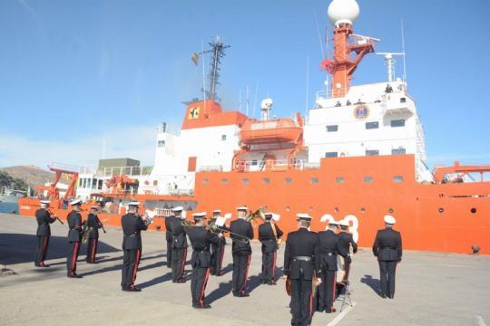 Con la distancia de seguridad la banda de música entona himnos navales para despedir al navio en su singladura