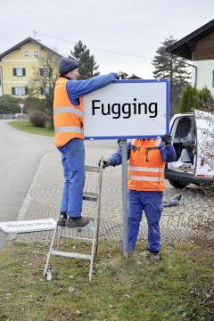 Operai sostituiscono il cartello di Fucking con quello recante il nuovo nome del luogo: Fugging.